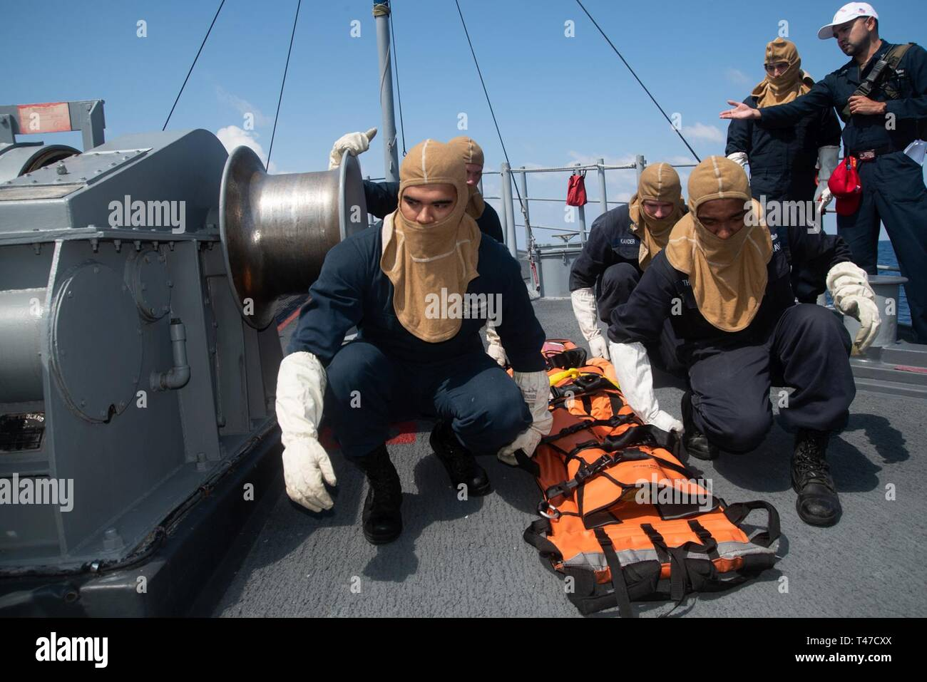SOUTH CHINA SEA (March 15, 2019) Sailors prepare to lift a stretcher during a general quarters drill aboard the Avenger-class mine countermeasures ship USS Chief (MCM 14). Chief, part of Mine Countermeasure Squadron 7, is operating in the Indo-Pacific region to enhance interoperability with partners and serve as a ready-response platform for contingency operations. - Stock Image
