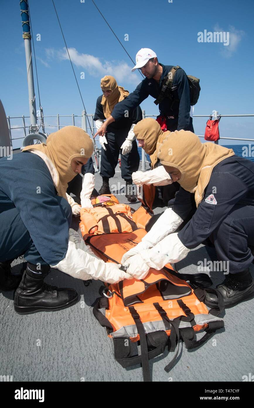 SOUTH CHINA SEA (March 15, 2019) Sailors secure a dummy to a stretcher during a general quarters drill aboard the Avenger-class mine countermeasures ship USS Chief (MCM 14). Chief, part of Mine Countermeasure Squadron 7, is operating in the Indo-Pacific region to enhance interoperability with partners and serve as a ready-response platform for contingency operations. - Stock Image