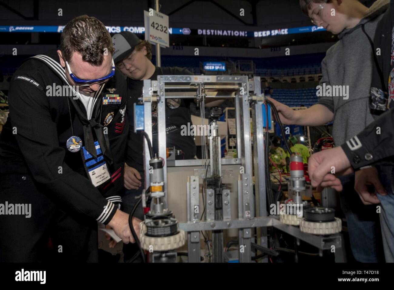 LOUIS (March 15, 2019) Navy Counselor 1st Class Andrew Foster, assigned to Navy Recruiting District (NRD) St. Louis, places a U.S. Navy sticker on an Alton High School, Ill., robot during the For Inspiration and Recognition of Science and Technology (FIRST) Robotics St. Louis regional competition, March 15, 2019. FIRST Robotics is an international high school robotics competition held each year in which teams of high school students, coaches, and mentors build game-playing robots which complete tasks such as scoring balls into goals, flying discs into goals, inner tubes onto racks, hanging on  Stock Photo