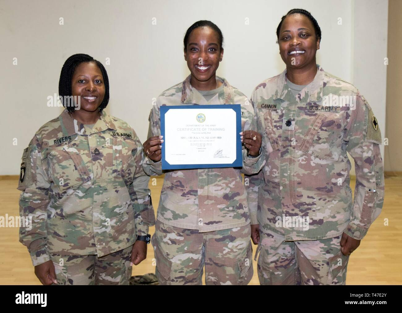 U.S. Army Sgt. 1st Class Tara Rivers, Equal Opportunity Advisor and instructor, 1st Theater Sustainment Command, right, poses with Master Sgt. Shakka Bradford, HHC supply noncommissioned officer in charge 335th Signal Command (Theater) (Provisional), center, and U.S. Army Lt. Col. Laketta Cannon, Assistant Chief of Staff G1 1st Theater Sustainment Command, right, following the Equal Opportunity Leaders Course 19-06 graduation ceremony at Camp Arifjan, Kuwait, March 17, 2019. - Stock Image