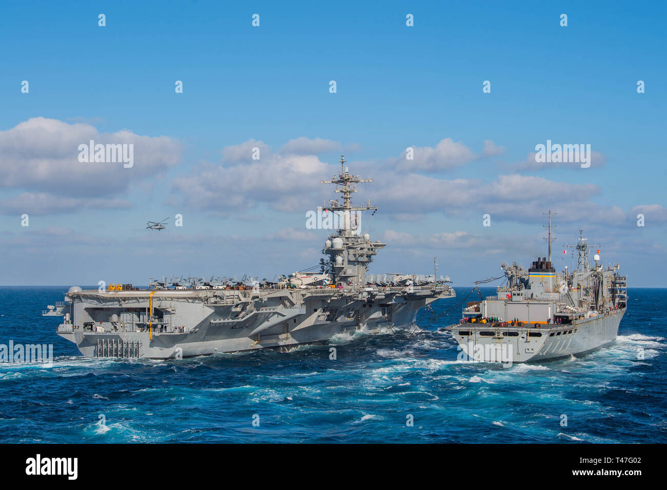 190412-N-DS741-0042 ATLANTIC OCEAN (April 12, 2019) The Nimitz-class aircraft carrier USS Abraham Lincoln (CVN 72) conducts a replenishment-at-sea (RAS) with the fast combat support ship USNS Arctic (T-AOE-8). Abraham Lincoln is underway as part of the Abraham Lincoln Carrier Strike Group (ABECSG) deployment in support of maritime security cooperation efforts in the U.S. 5th, 6th and 7th Fleet areas of responsibility. With Abraham Lincoln as the flagship, deployed strike group assets include staffs, ships and aircraft of Carrier Strike Group 12 (CSG 12), Destroyer Squadron 2 (DESRON 2), USS Le - Stock Image