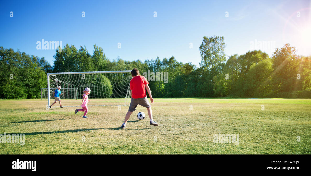Boys playing football on the field with gates - Stock Image