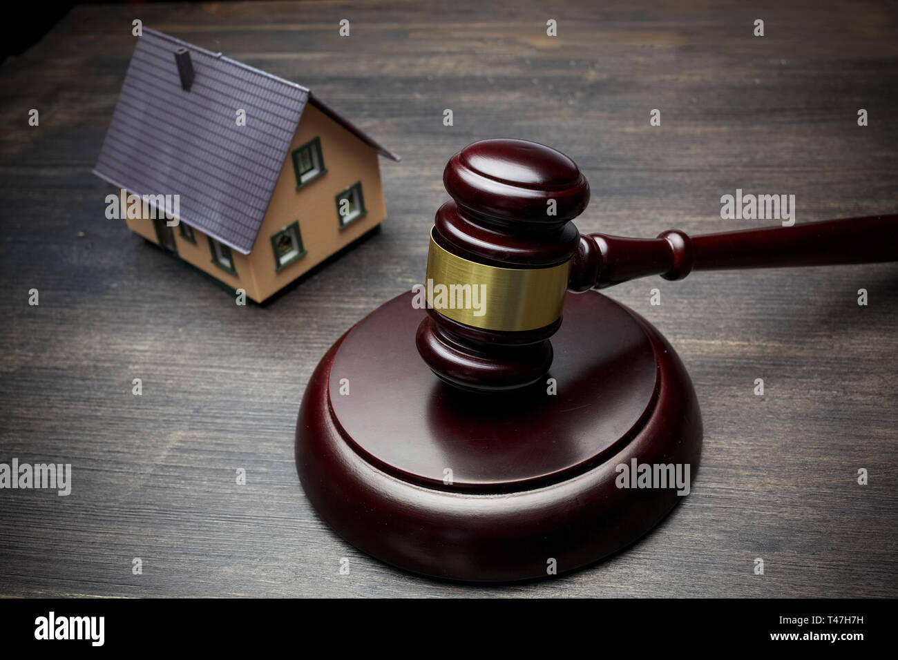hammer of the judge, the house on a black wooden background. real estate. Stock Photo
