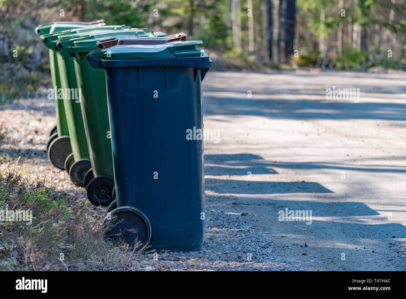 Trash cans standing beside a gravel road in Filipstad Varmland Sweden spring 2019 - Stock Image
