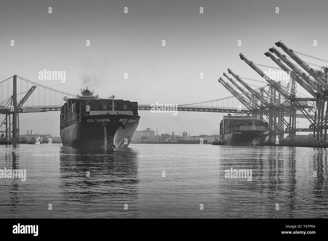 Black & White Photo Of Container Ship, KOTA CAHAYA, Pumping Ballast Water Overboard (De-Ballasting), As She Departs The Port Of Los Angeles At Dawn. - Stock Image