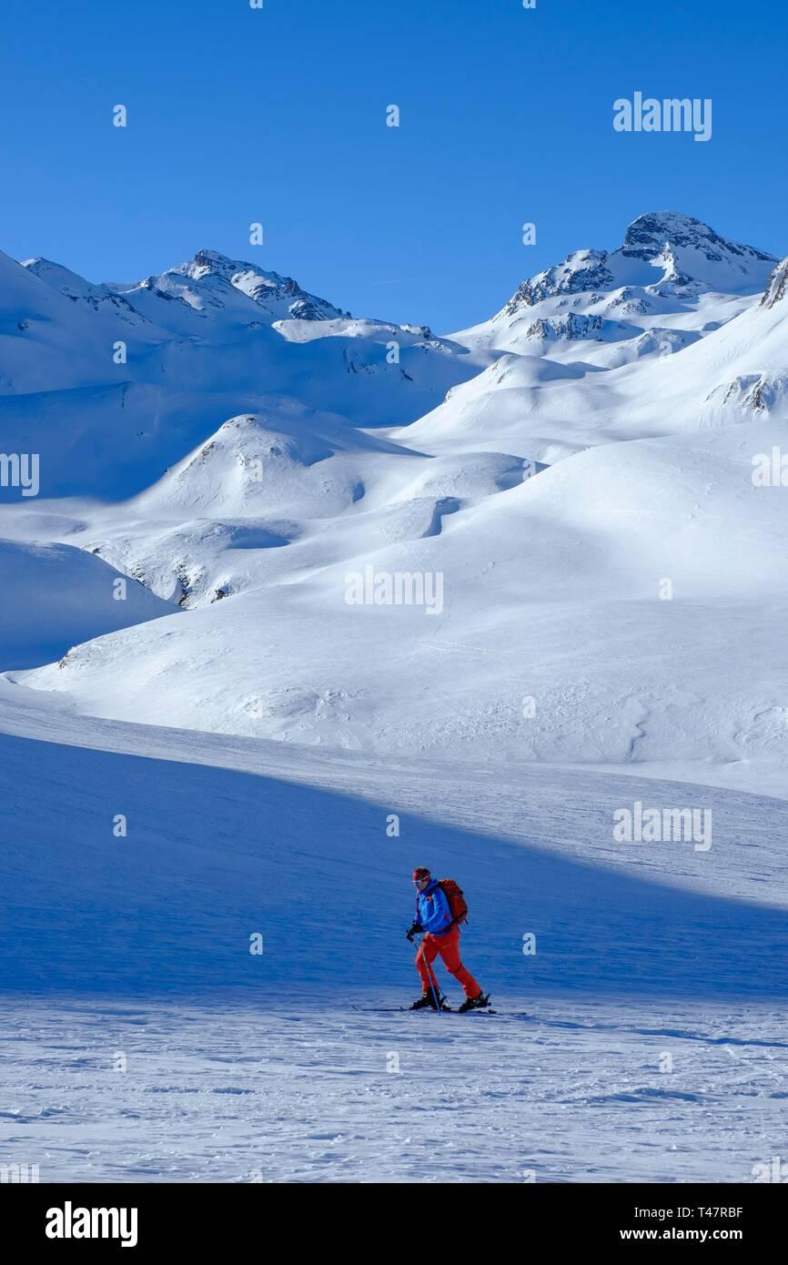 Ski tourer ascending Ils Chalcogens, in the background Piz Tasna and Breite Krone, Graubunden, Switzerland - Stock Image