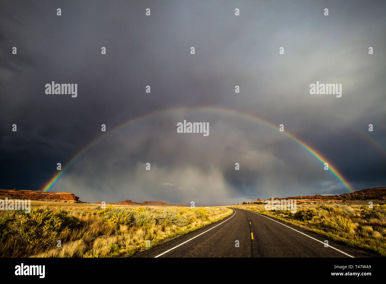 A full rainbow and thuderstorm clouds over Scenic Highway 211 in Canyonlands National Park, Southeast Utah, USA. Stock Photo