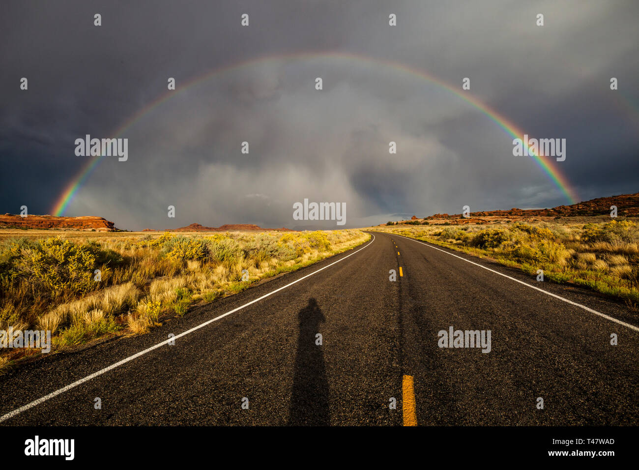 The shadow of the photographer shows on the road below a full rainbow and thuderstorm clouds over Scenic Highway 211 in Canyonlands National Park, Sou Stock Photo