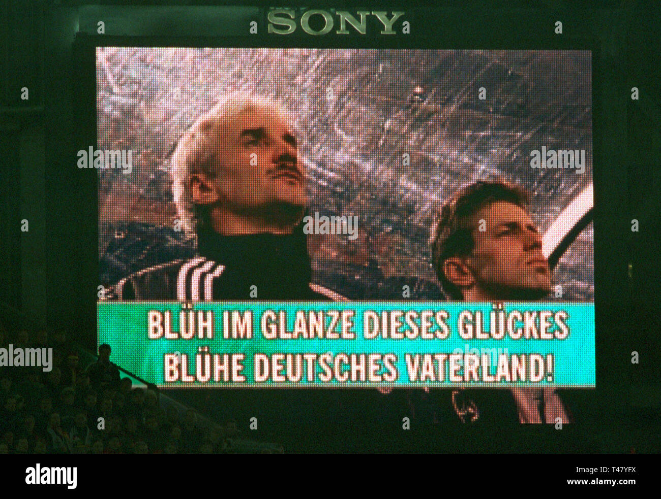 Westfalenstadion Dortmund Germany 14.11.2001, Football qualifier for the FIFA World Cup 2002, Germany (white) vs Ukraine (blue) --- German coaches Rudi VOELLER and Michael SKIBBE on video wall with lyrics of German national anthem : BlŸh (Blueh) im Glanze dieses GlŸckes (Glueckes), BlŸhe (Bluehe) Deutsches Vaterland), Flourish in the radiance of this fortune,   Flourish, German fatherland! Stock Photo