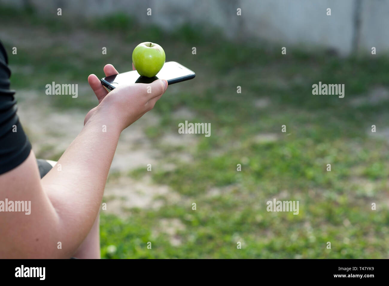Hand boy teenager holding a mobile phone IPhone 6s. The concept of attribute necessity, the cult of values of the younger generation. - Stock Image