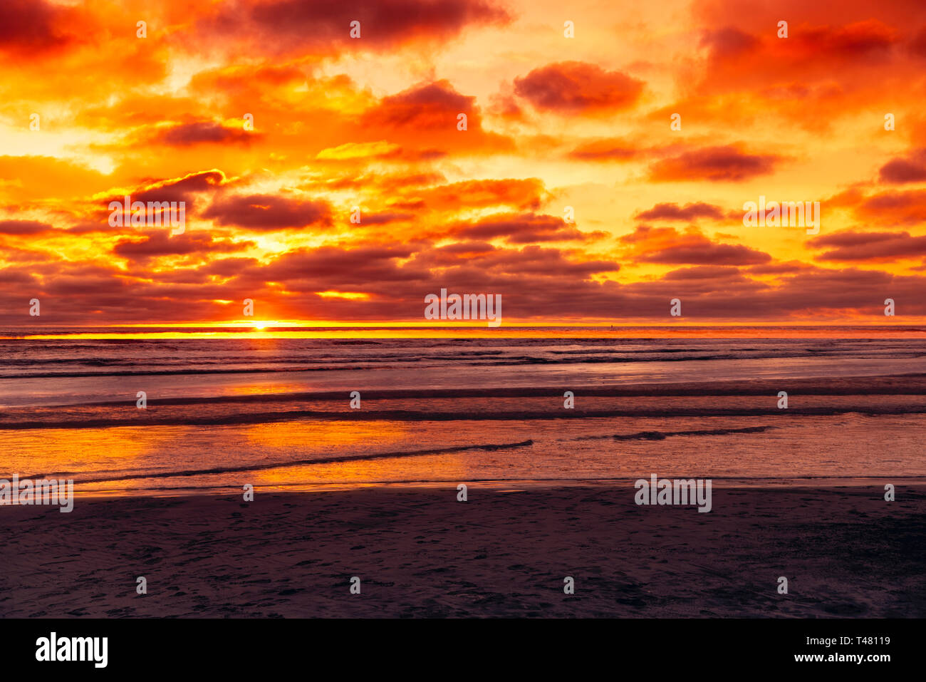 Waves rolling onto beach as sun is setting into ocean beyond, orange and yellow sky. - Stock Image