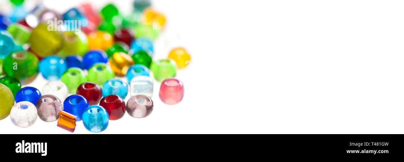 Close up on colorful translucent beads isolated on panoramic white background - Stock Image