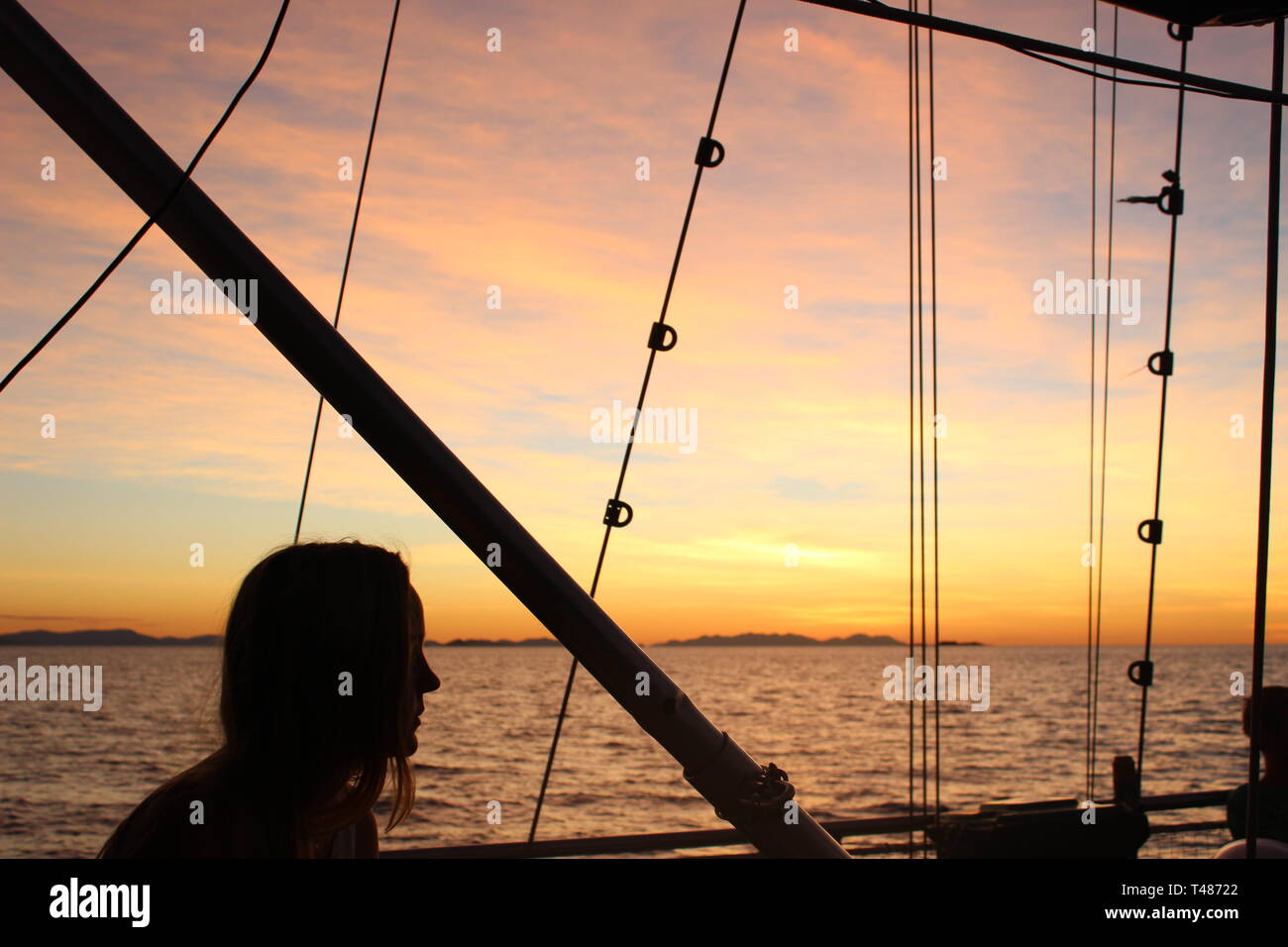 Watch the sunset from a sailing boat in the Whitsundays, Australia - Stock Image