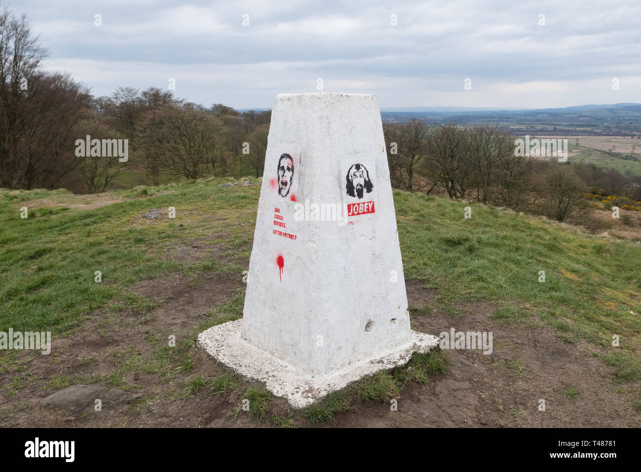 white trigpoint with stencil graffiti - Castle Hill Hillfort, nr Bar Hill Fort, Antonine Wall,  Twechar, East Dunbartonshire, Scotland, UK - Stock Image