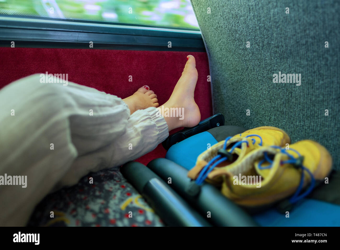 Feet of a yound child who is relaxing in a bus after a long day Stock Photo