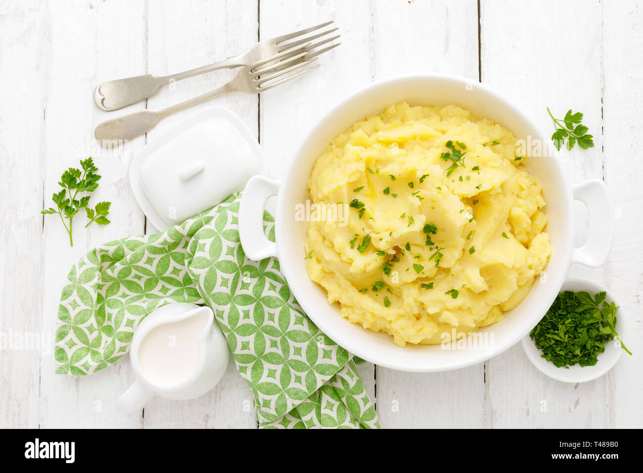 Mashed potato with butter and milk on table - Stock Image