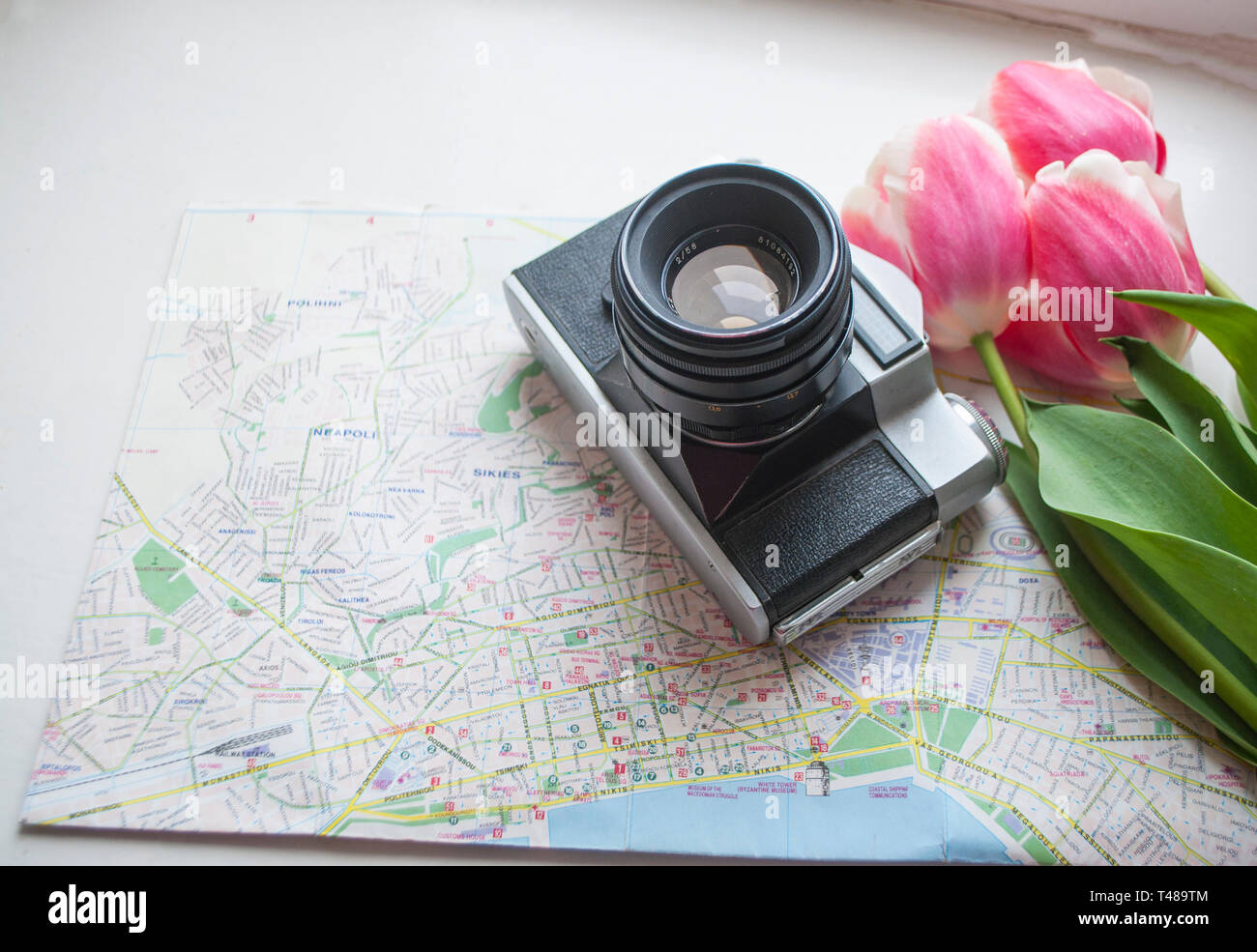 Flat lay of map, camera and tulips boquet. Travel concept. - Stock Image
