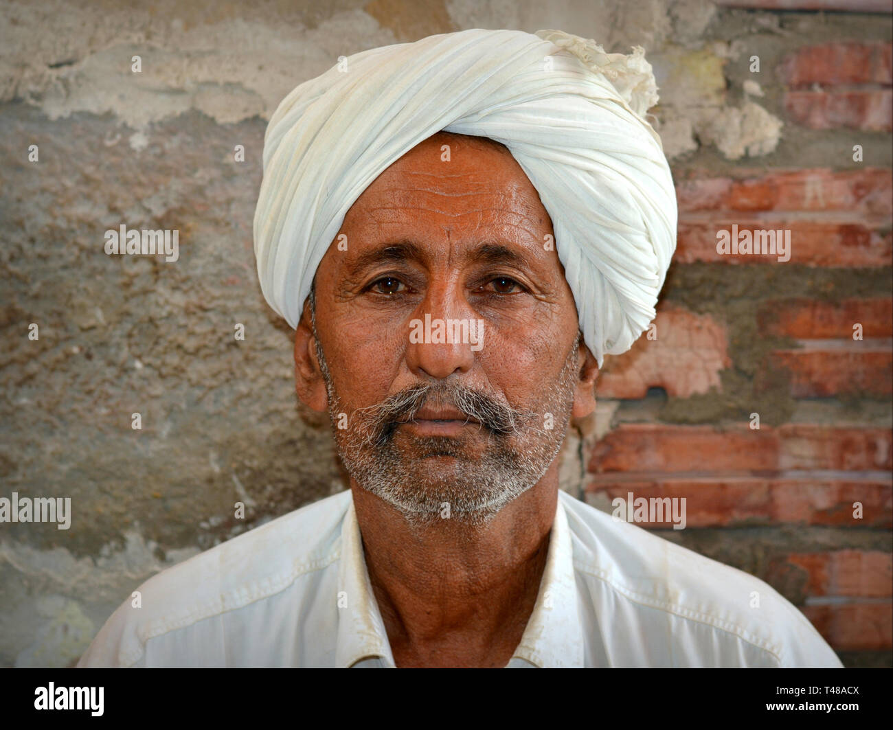 Tribal chief from the Thar Desert wears his signature headdress, a white Rajasthani turban (pagari) and poses for the camera. - Stock Image