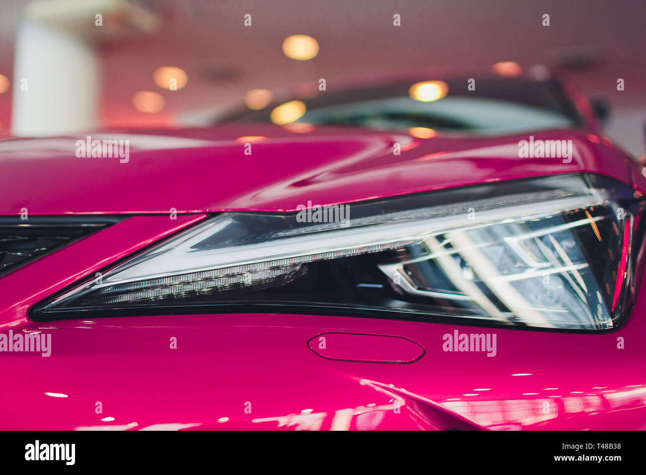 Close up shot headlight in luxury pink car background. Modern and expensive sport car concept. Stock Photo
