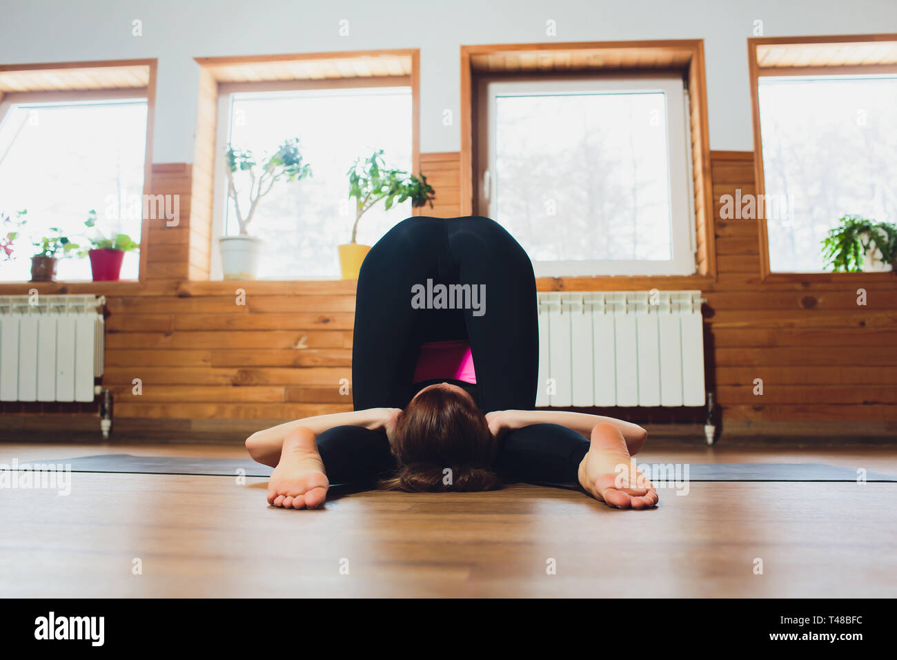 Young sporty attractive woman practicing yoga, doing asana paired with Cat Pose on the exhale exercise, Cow, Bitilasana pose, working out, wearing - Stock Image