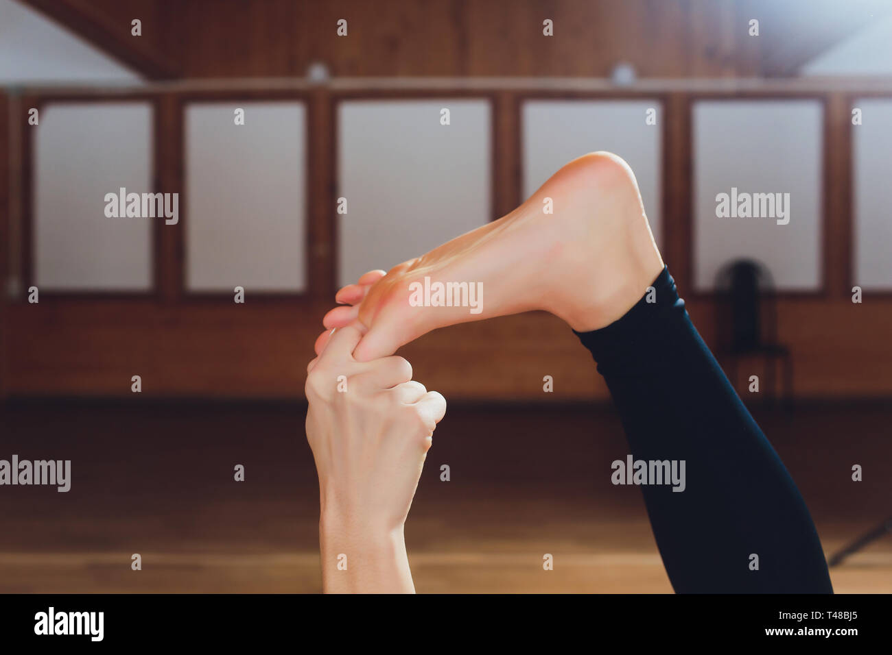 Beautiful young model working out at home, doing yoga exercise on floor, lying in Parivrtta Supta Padangushthasana, reclined variation of Twisting - Stock Image