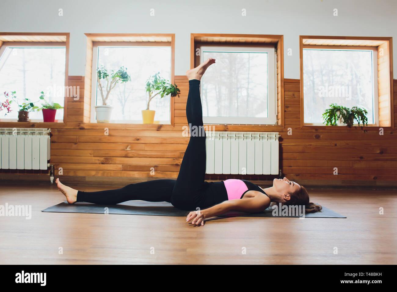 Young yogi sporty woman working out, warming up using yogic belt, lying in yoga Supta Padangushthasana, One Leg Lift exercise, reclined variation of - Stock Image