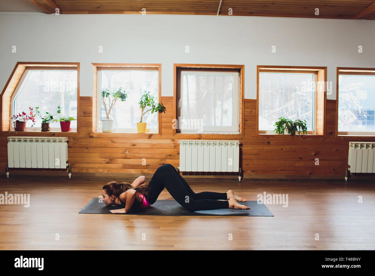 Woman doing Ashtanga Vinyasa yoga Surya Namaskar Sun Salutation asana Adhomukha svanasana - downward facing dog on yoga mat in studio. Stock Photo