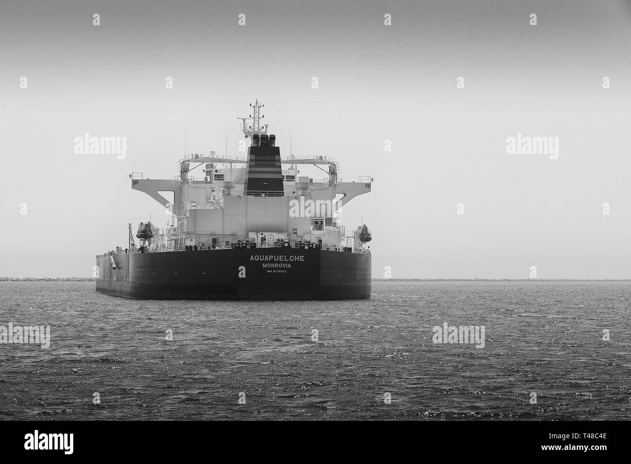 Black And White Photo Of The Stern Of The Supertanker, (Crude Oil Tanker), AQUAPUELCHE, Anchored In The Port Of Long Beach, California, USA. - Stock Image