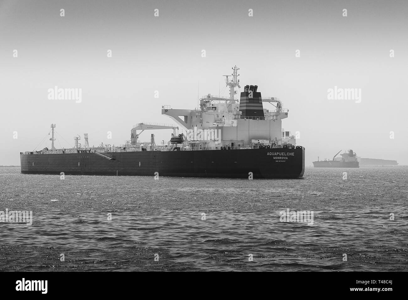 Black And White Photo Of The Supertanker, (Crude Oil Tanker), AQUAPUELCHE, Anchored In The Port Of Long Beach, California, USA. - Stock Image