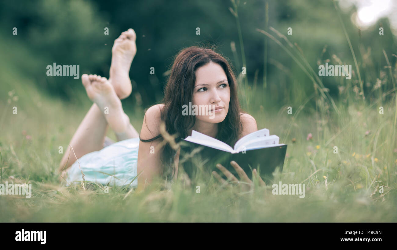 c8eeab46d9c charming young woman reading a book lying on the lawn . the concept of a  healthy
