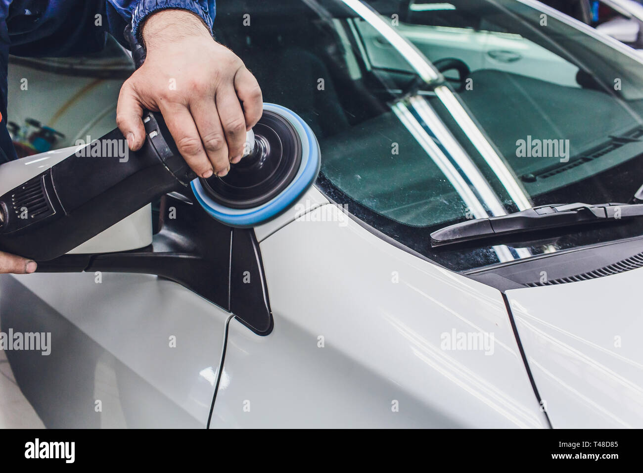 Car detailing - Hands with orbital polisher in auto repair shop. Selective focus. - Stock Image