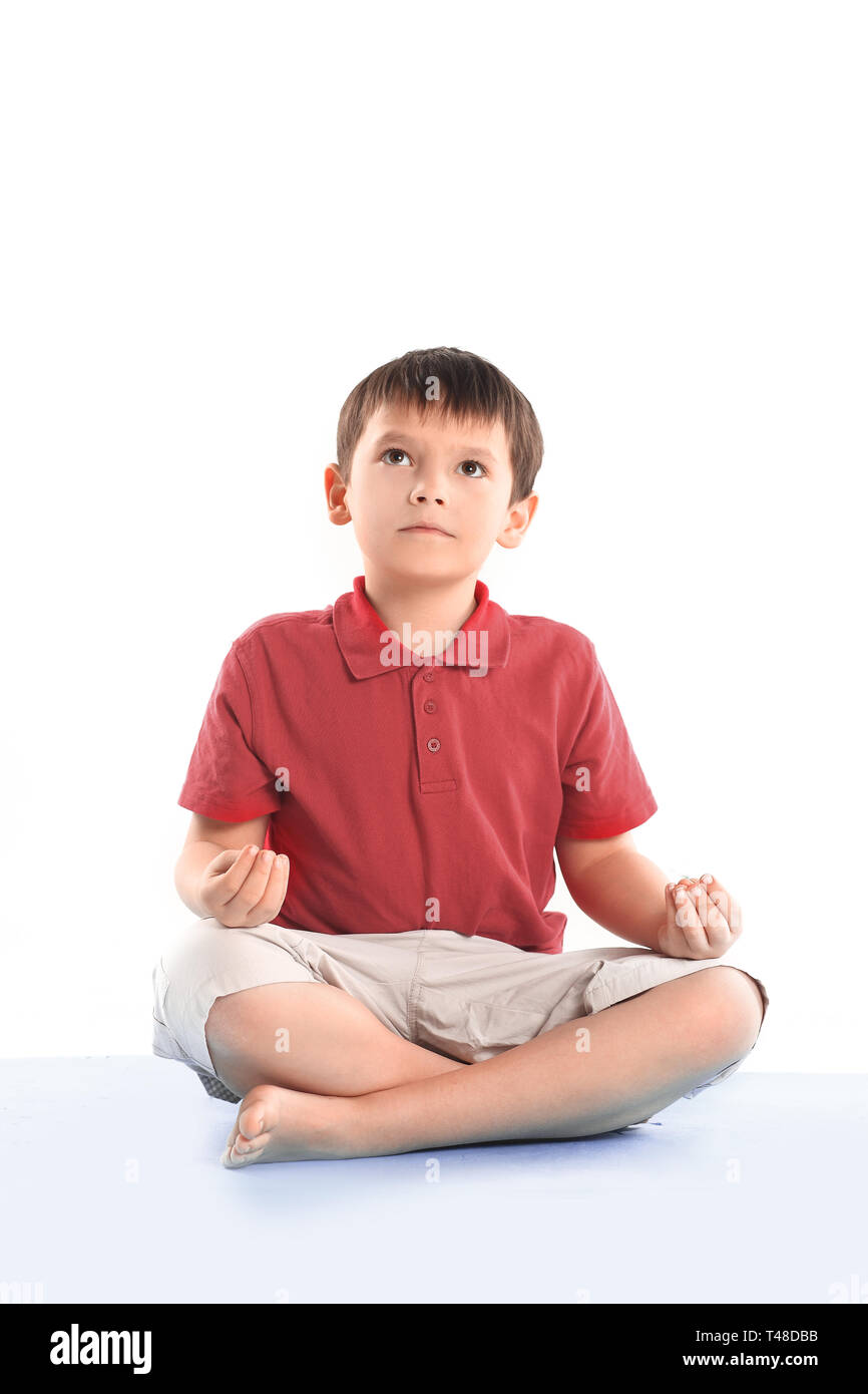 little boy is sitting in the Lotus position.isolated on white. - Stock Image