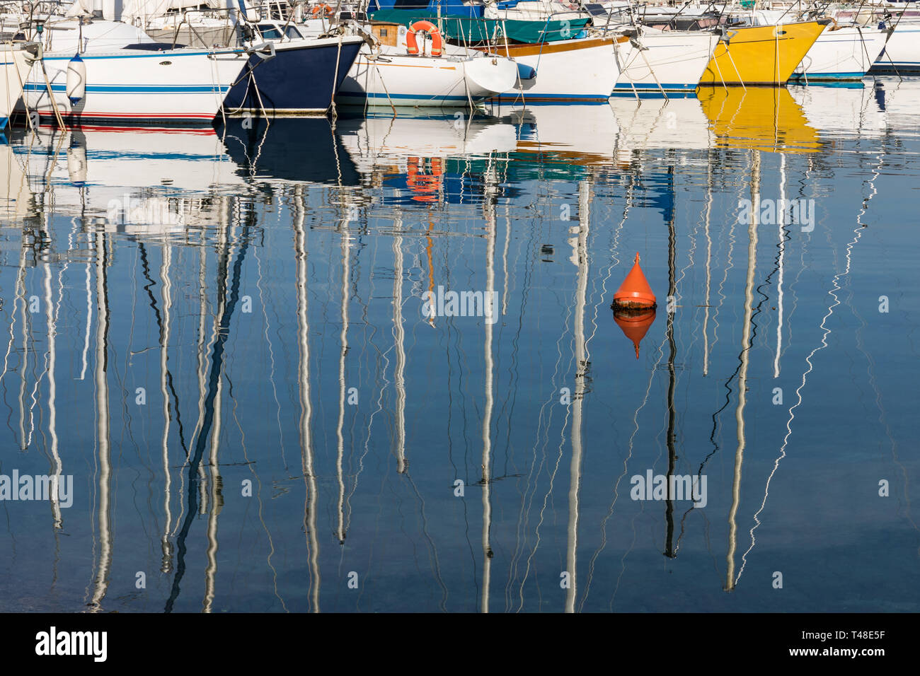 Colorful boats reflecting in the water - Stock Image