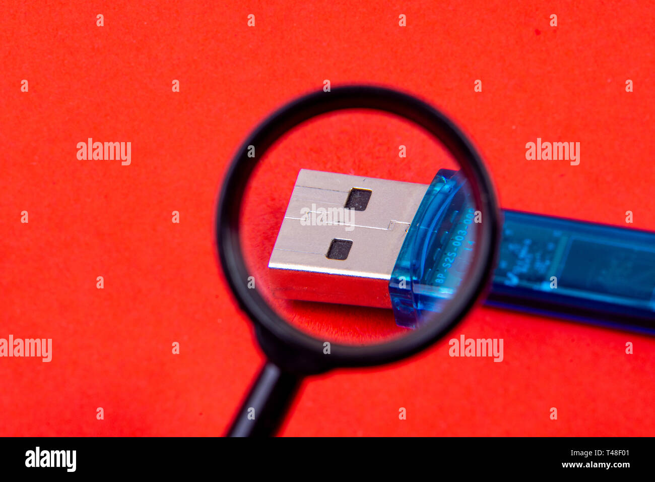 Data stick under the magnifying glass - search for clues - Stock Image