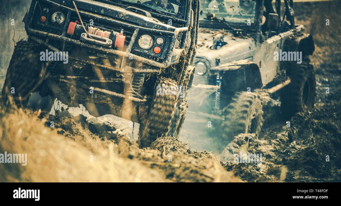 Off Road Trail Expedition. Two Sport Utility Vehicles Covered in Mud on the Rural Road. - Stock Image