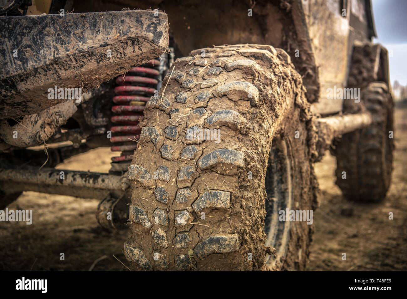 Off Roader Tire Closeup. SUV Wheel Covered by Clay and Mud. Motorsport Theme. Stock Photo