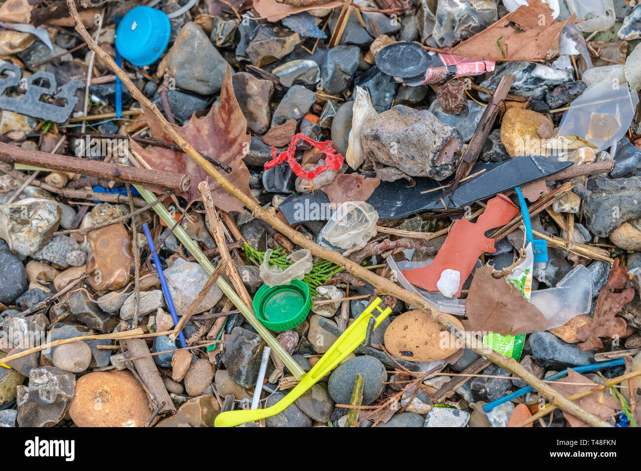 Plastic pollution found on the beach. The accumulation of plastic objects in the Earth's environment adversely affects wildlife and humans. - Stock Image