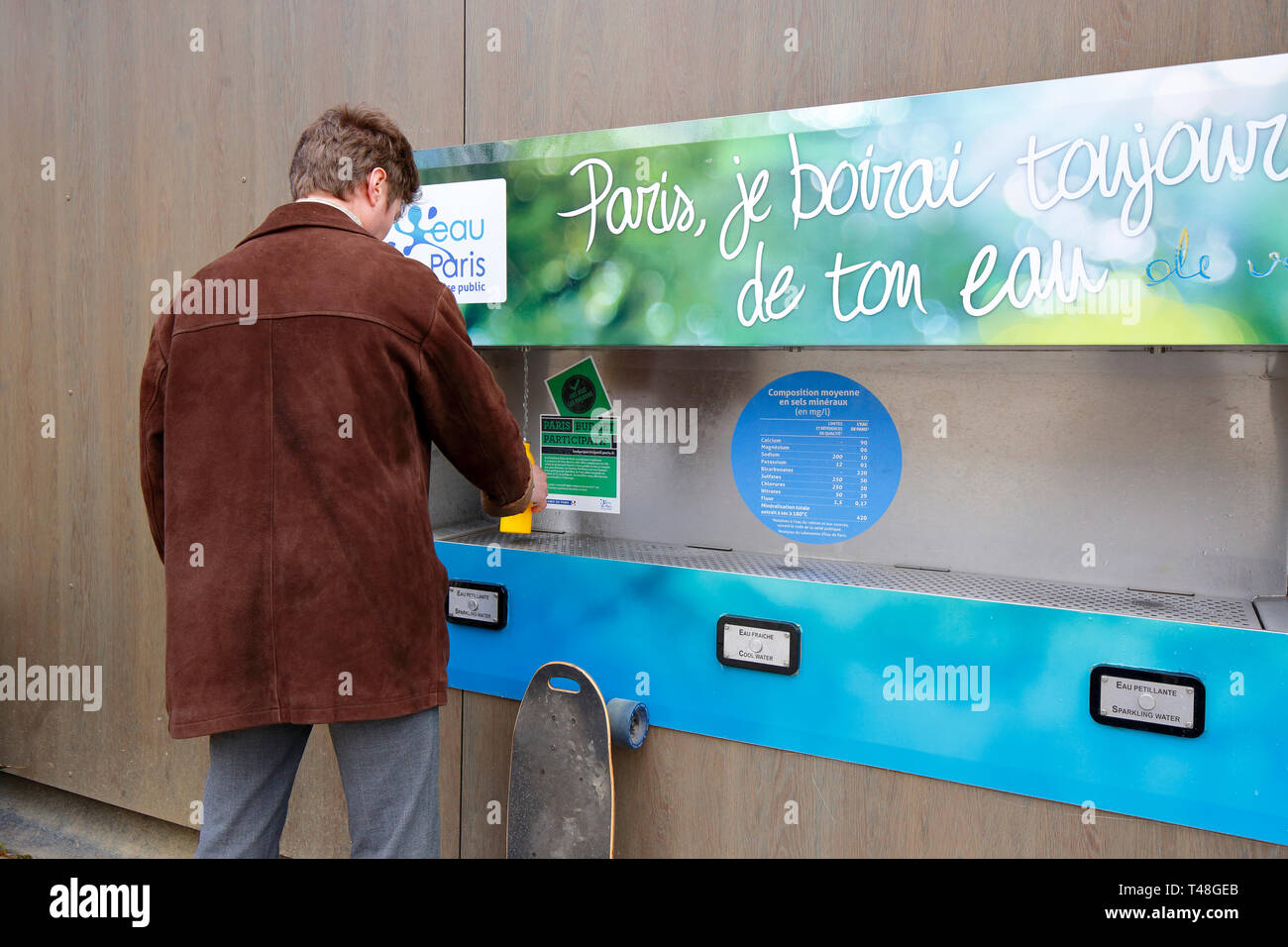 a-person-filling-a-bottle-with-carbonated-water-at-a-public-water-fountain-in-paris-T48GEB.jpg