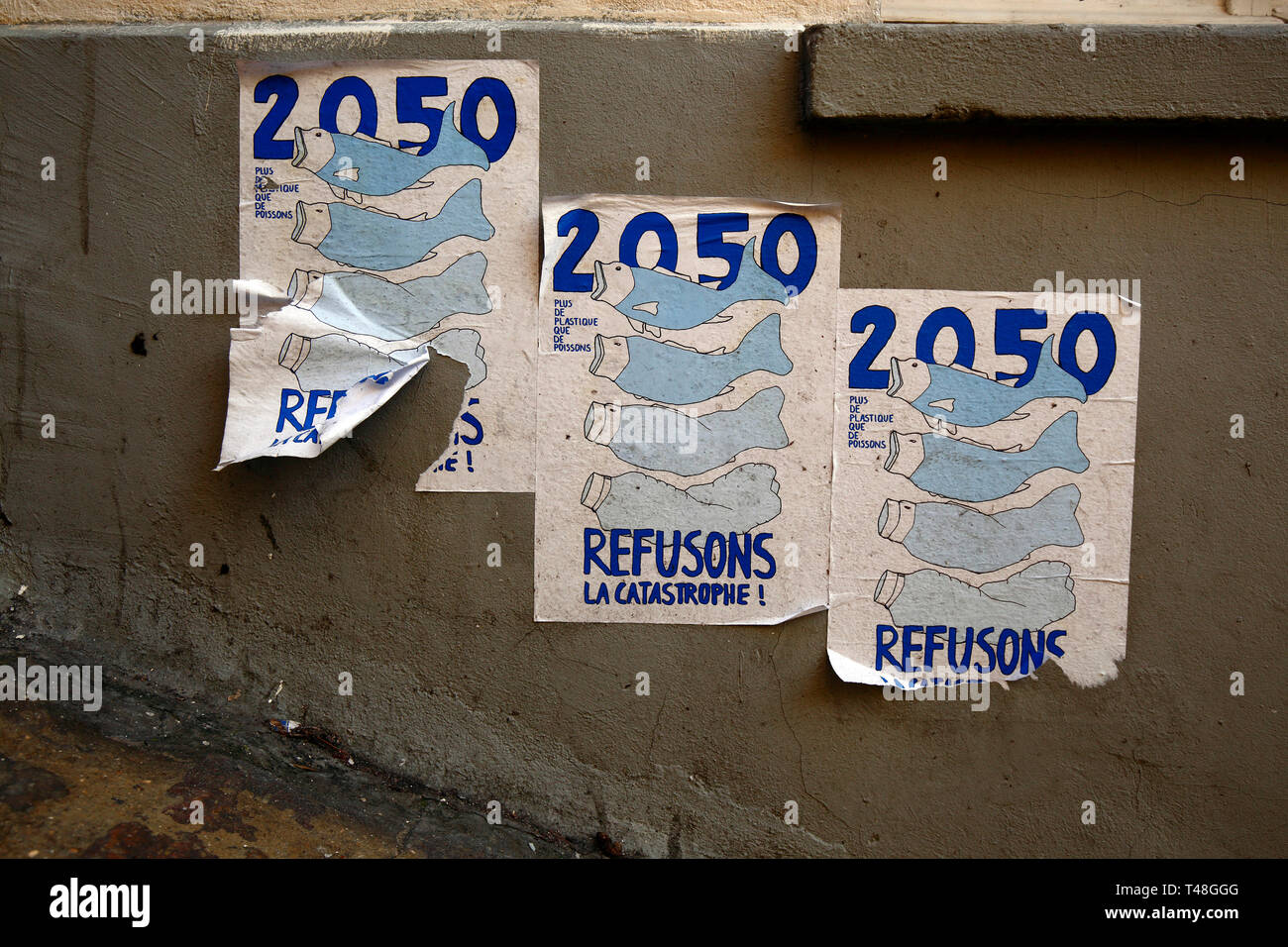 Flyers on a wall in Paris warning of an impending ocean plastic pollution crisis - Stock Image