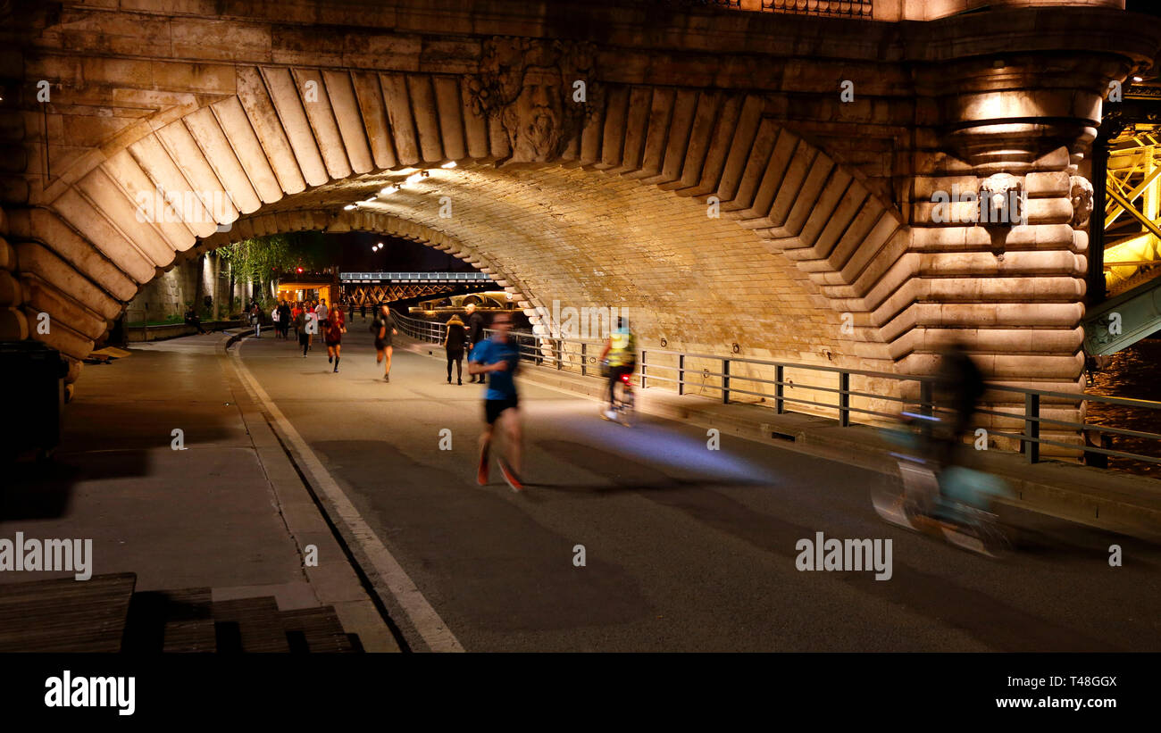 Evening joggers and bicyclists on the Voie Georges Pompidou passing under Pont Notre Dame, Paris - Stock Image