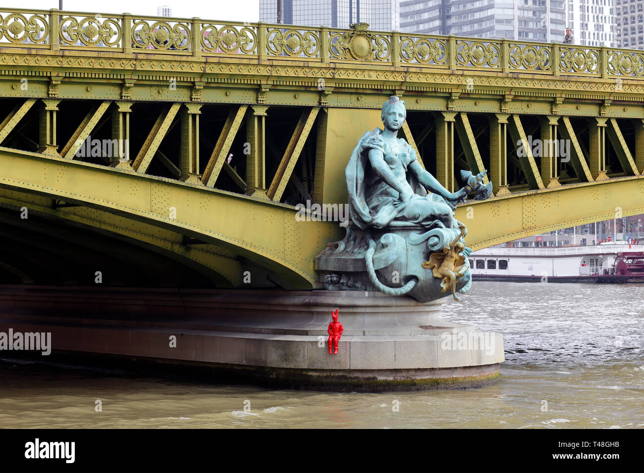 'Ville de Paris' one of four statues by Jean-Antoine Injalbert adorning Pont Mirabeau over the Paris Seine with an added red statue by street artist J - Stock Image