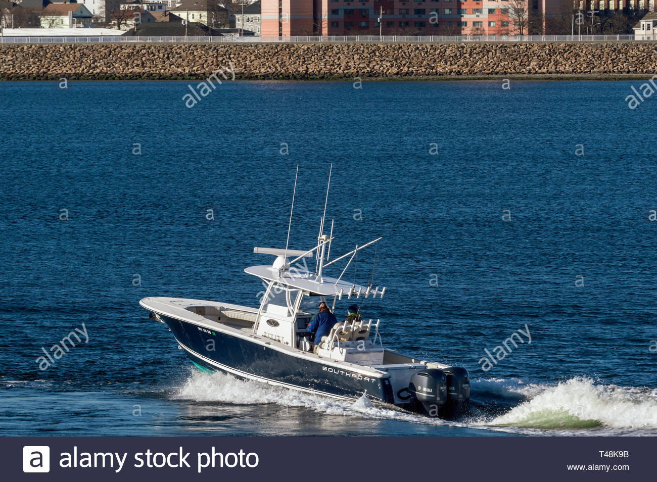 New Bedford, Massachusetts, USA - April 11, 2019: Center console boat with two outboard motors heading toward Buzzards Bay on chilly morning in early  - Stock Image