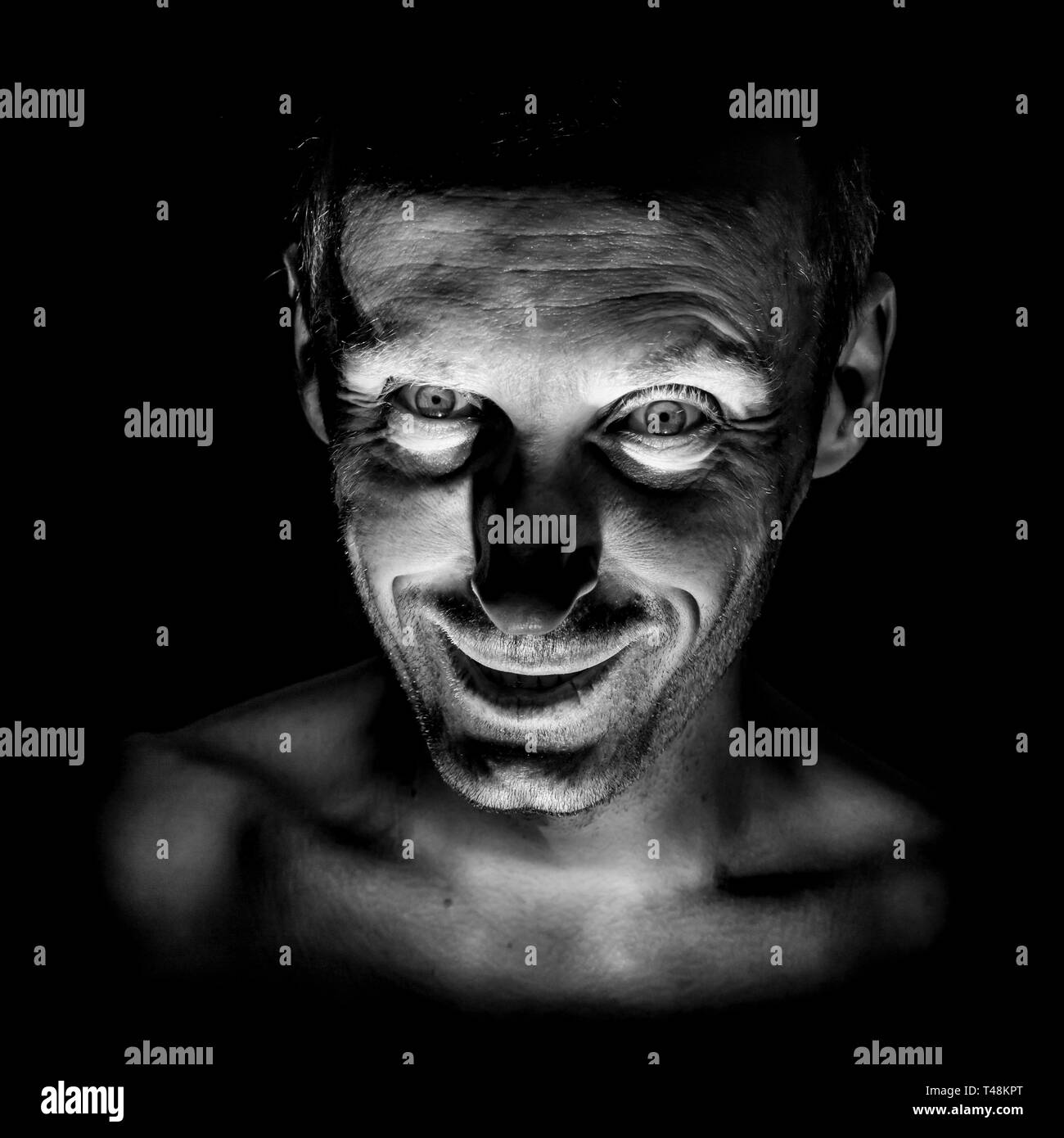 Portrait of smiling adult caucasian man. He smiles like maniac and seems like madness. Black and white shot, low-key lighting. Isolated on black. - Stock Image