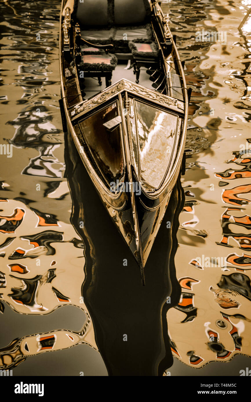 A gondola rests at dock surrounded by colorful reflections in Venice, Italy. - Stock Image