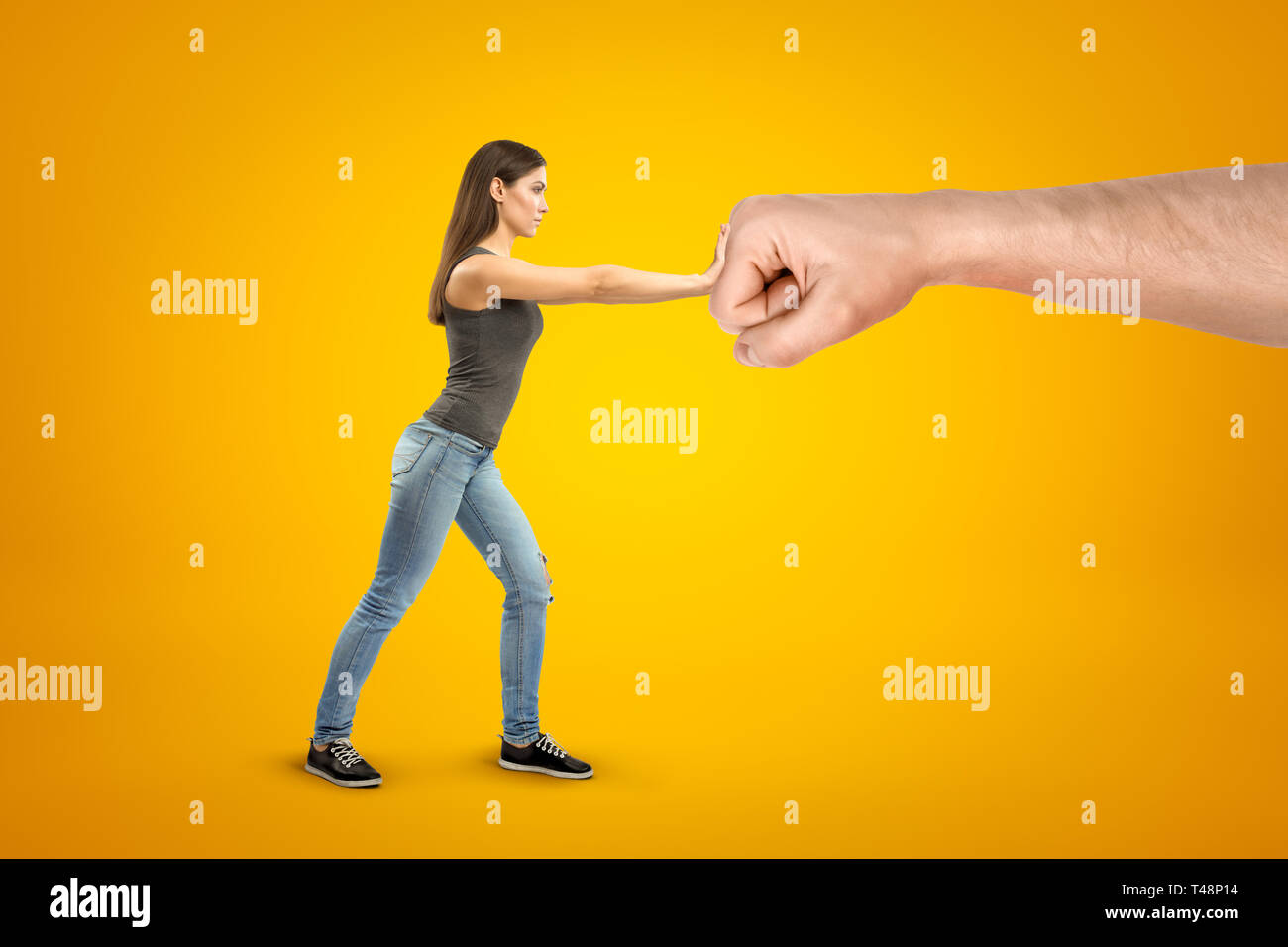 Young brunette girl wearing casual jeans and t-shirt making stop gesture against big male stretched fist on yellow background - Stock Image