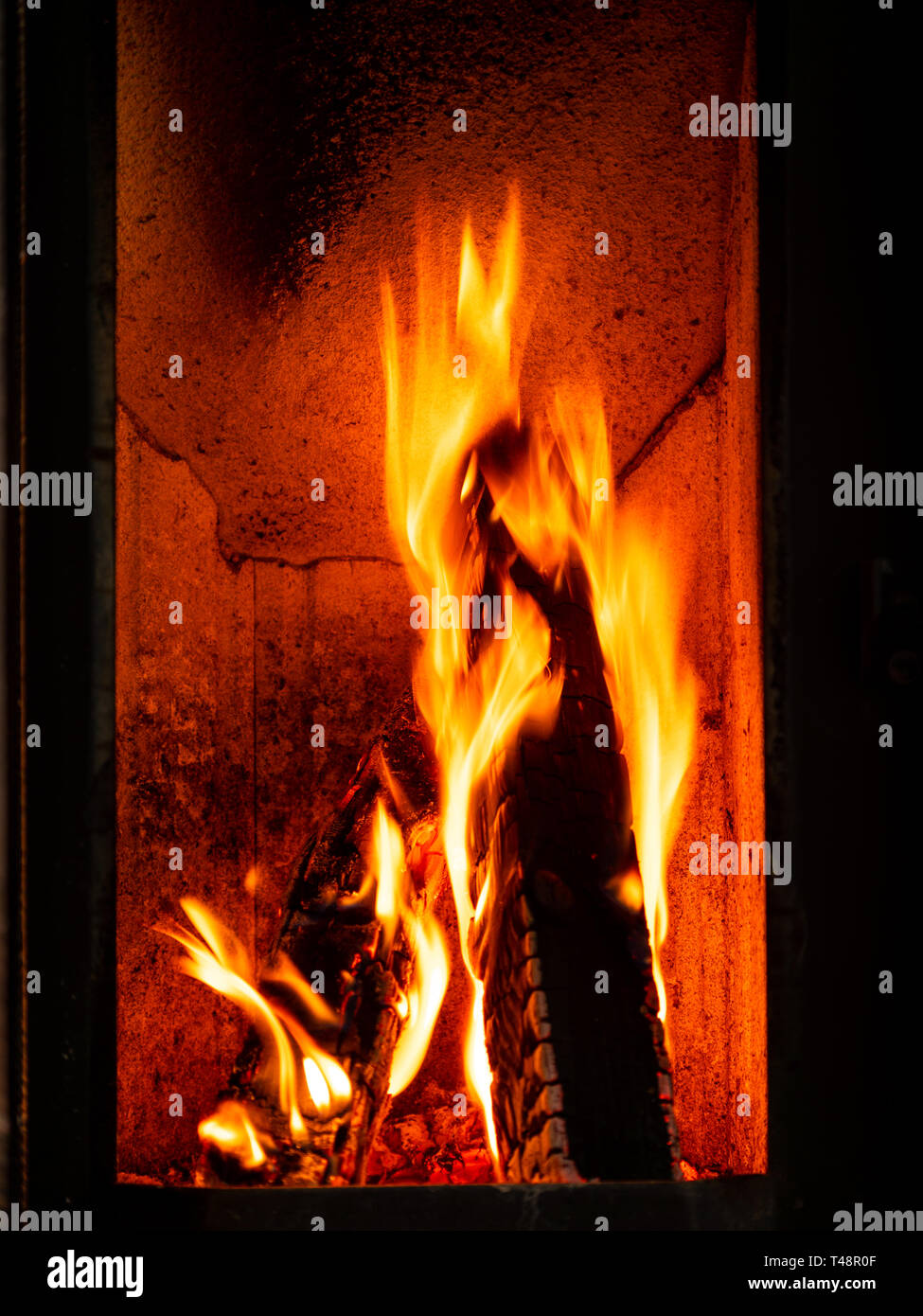 Image of burning wood logs in fire place - Stock Image