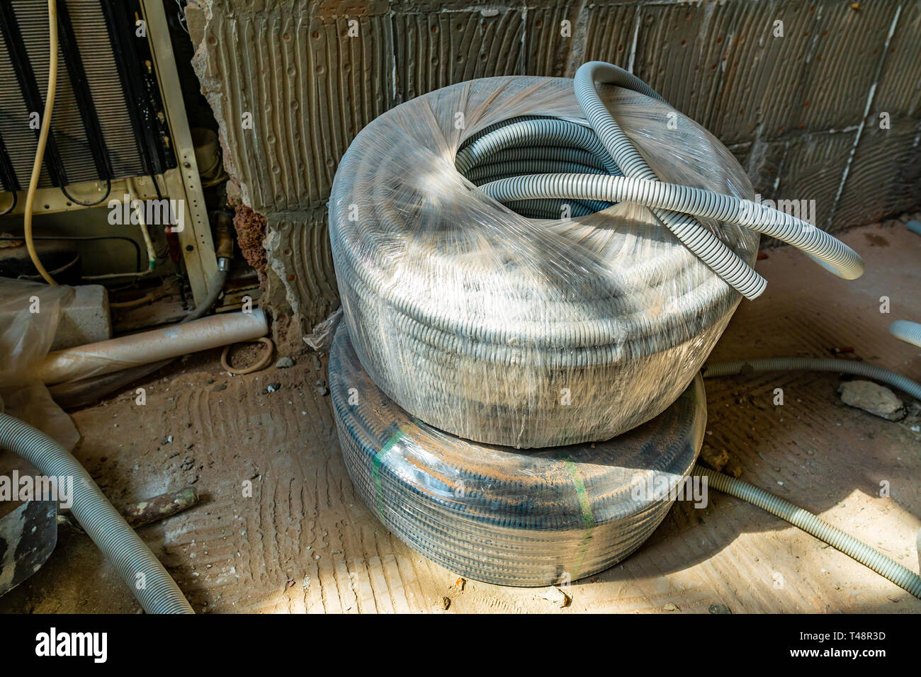 Light Grey Colored Electrical Power PVC Pipe Hose Under Construction Staggered on Floor Packed and Covered in a Plastic Bag - Stock Image