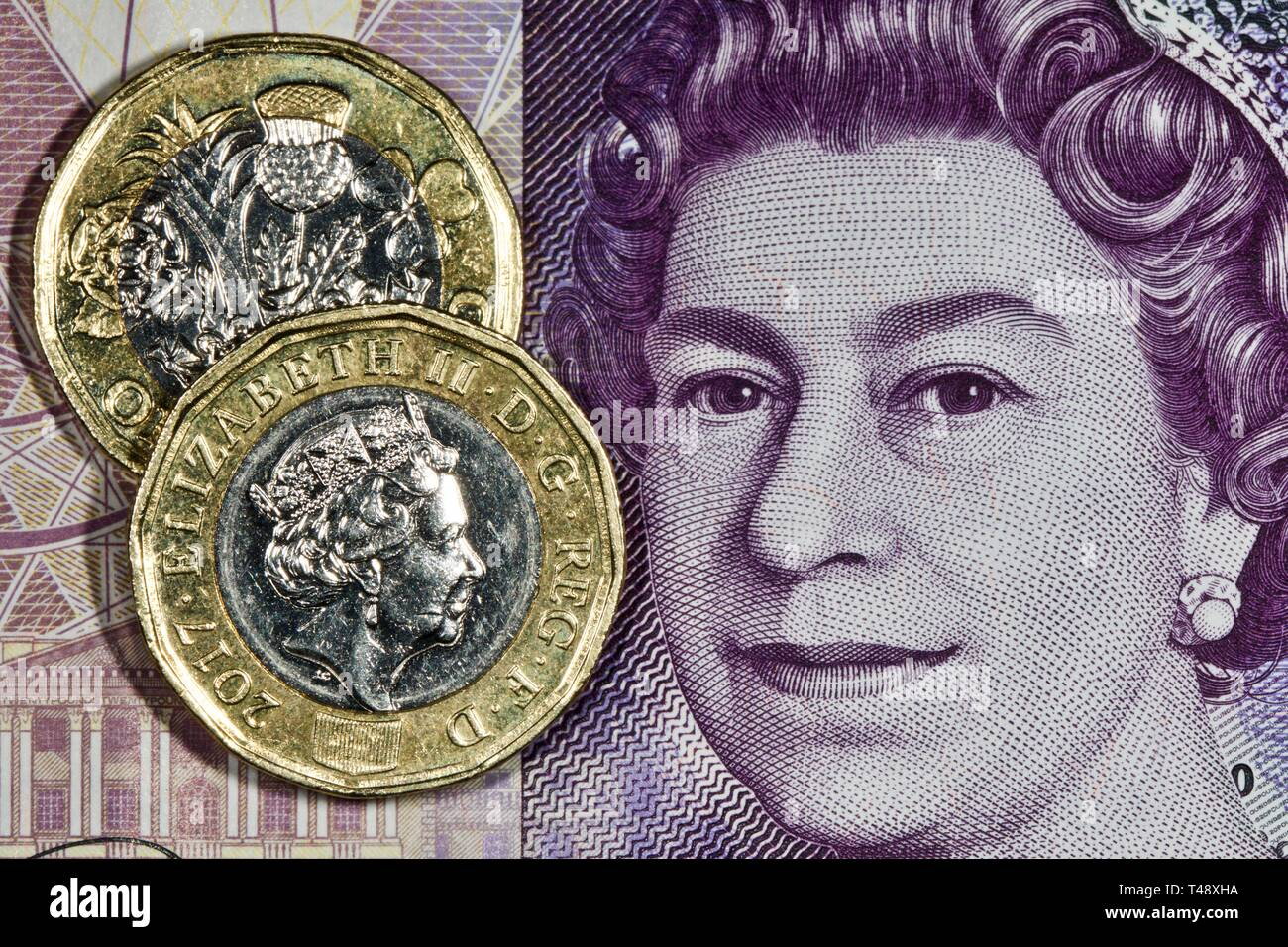 New one pound coins on a twenty pound banknote - Stock Image