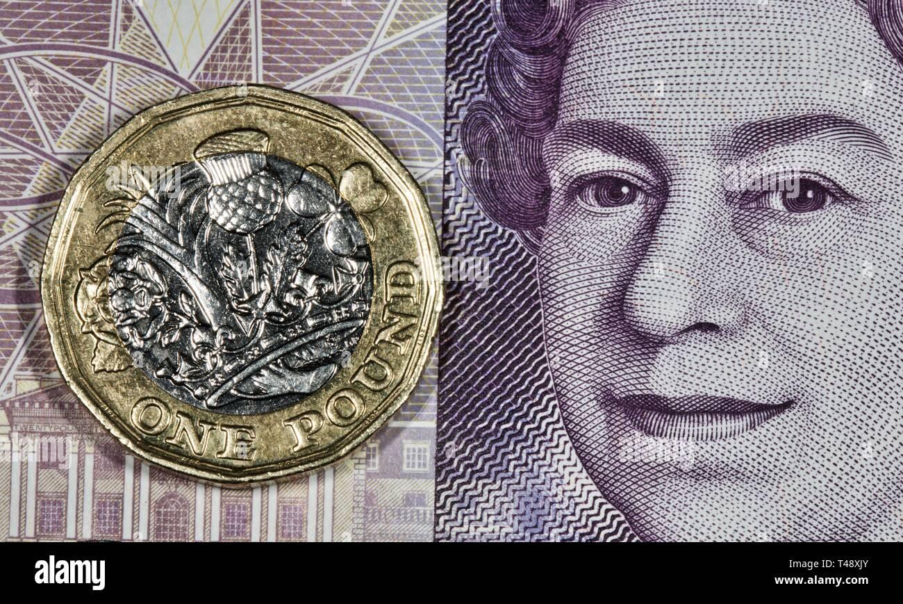 £1 pound coin on a twenty pound banknote Stock Photo