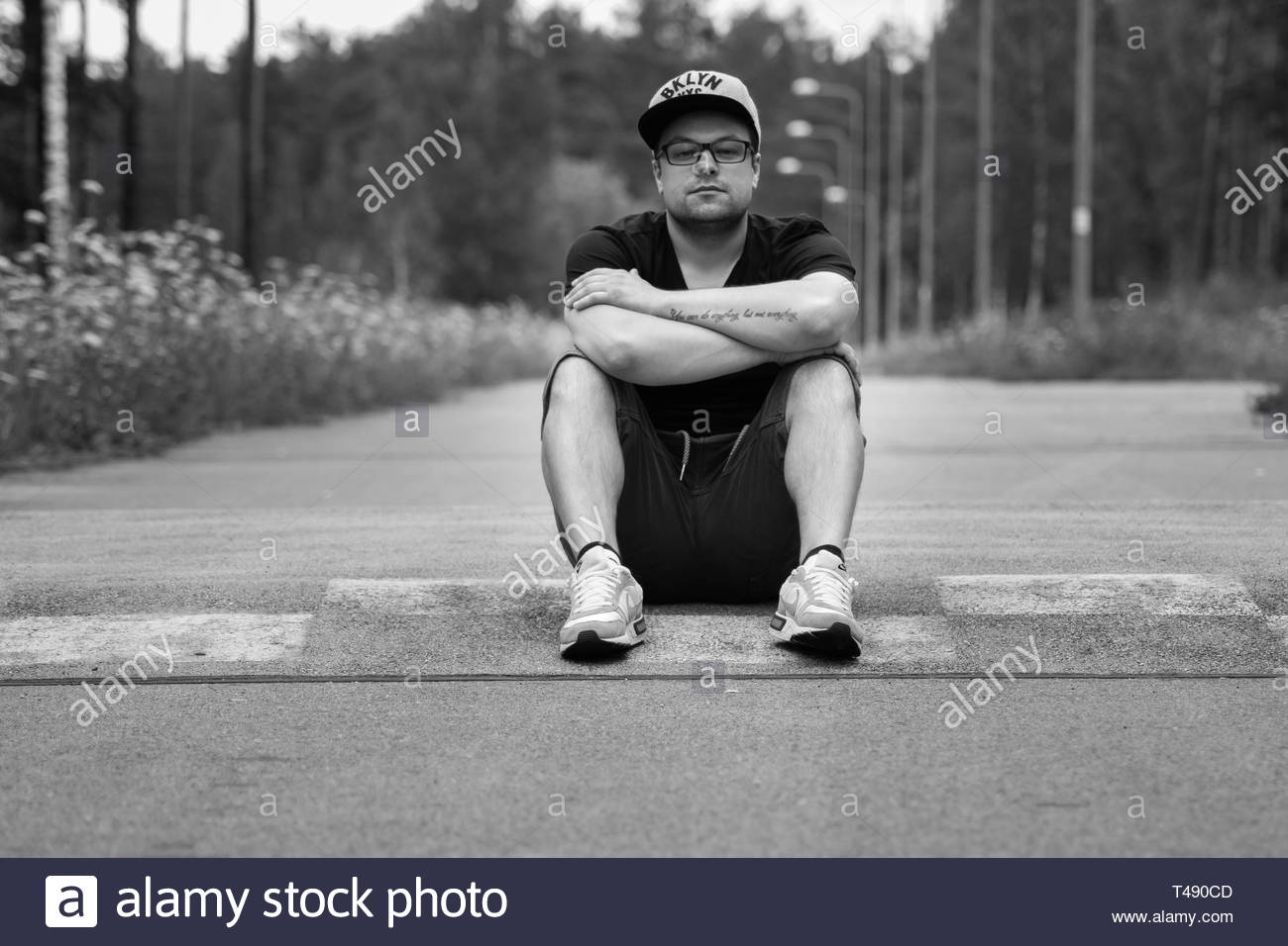 person sits on road - Stock Image